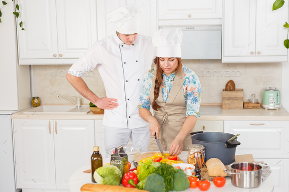 A senior chef giving cooking lesson to young chefs - Stock Photo - Images