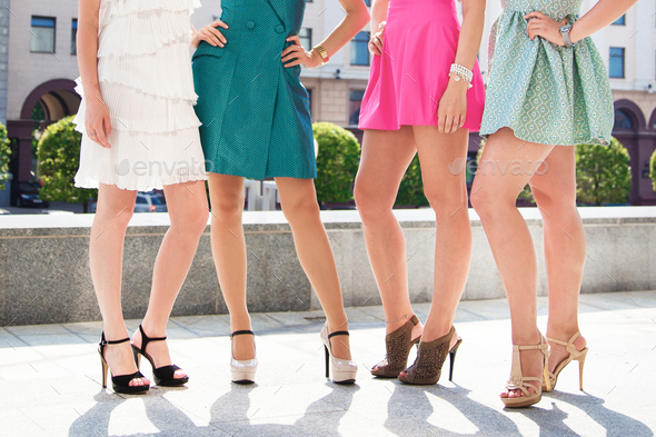 girls women friends with sexy tanned legs standing - Stock Photo - Images