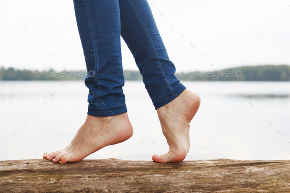 Womans feet walking on a log - Stock Photo - Images