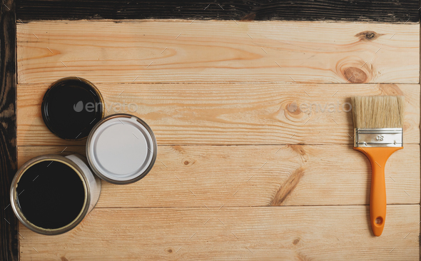 Two paint tins and brush on wooden background with copy space in center, top view - Stock Photo - Images