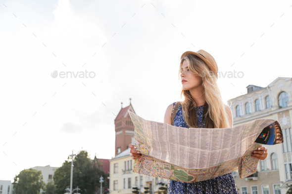 stylish traveler hipster woman portrait with camera and hat holding map on the street - Stock Photo - Images