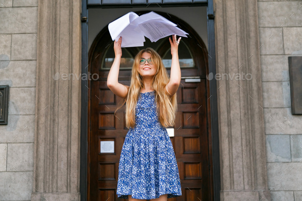 Young woman threw the papers in casual and paper flying in air. Freedom success concept - Stock Photo - Images