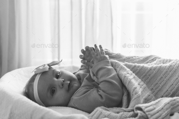 Little cute baby girl lying in basket - Stock Photo - Images