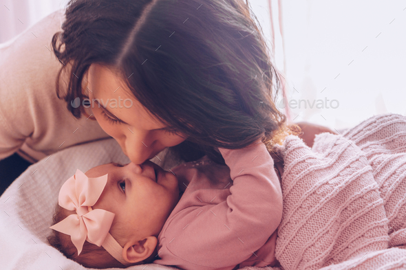 Young mother kissing her adorable baby girl. - Stock Photo - Images
