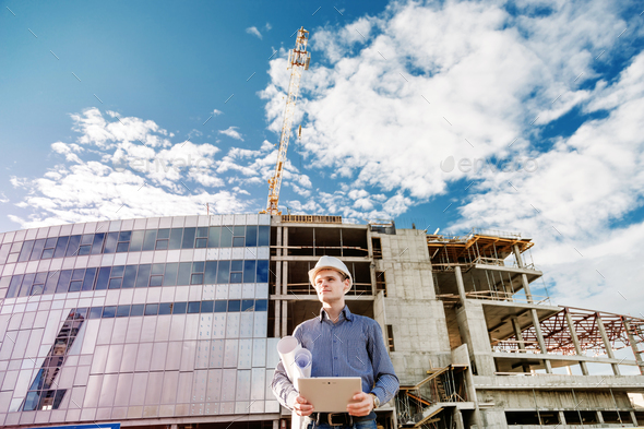 Construction manager controlling building site with plan - Stock Photo - Images