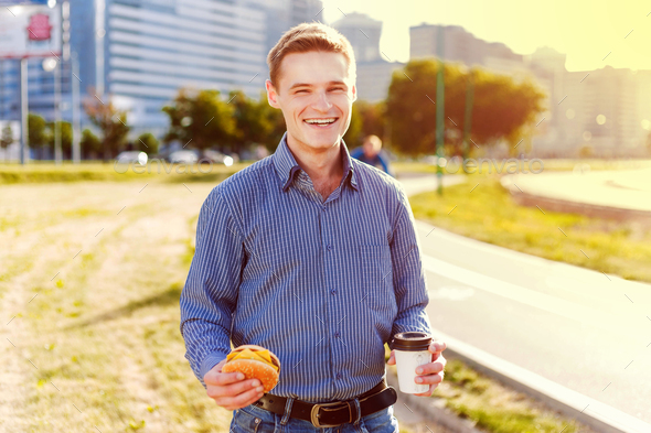 Man bites freelancer sandwich with coffee - Stock Photo - Images