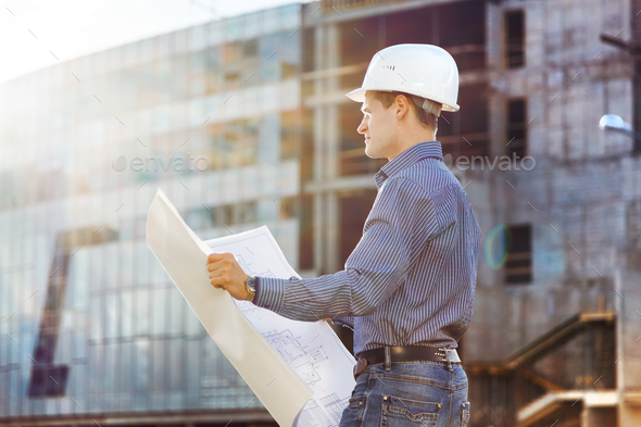 Architect in helmet with blueprints looks at camera in a building site - Stock Photo - Images
