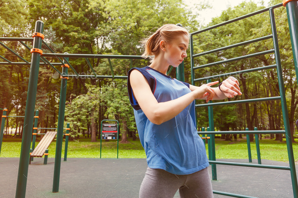 Woman using activity tracker at gym - Stock Photo - Images