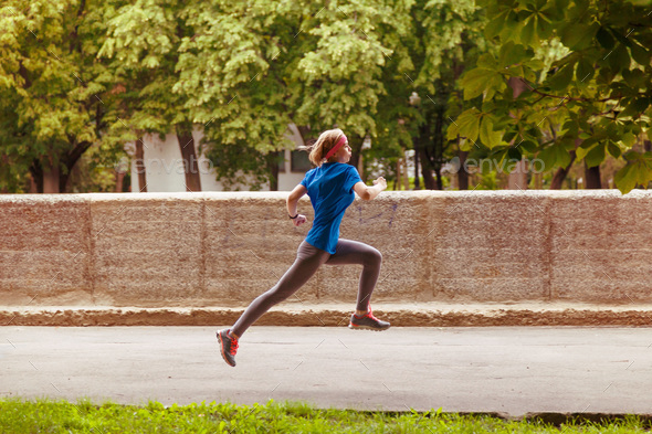 Young sporty woman running in the summer city park - Stock Photo - Images