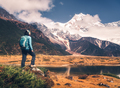 Standing young woman with backpack and mountains - PhotoDune Item for Sale