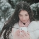 Portrait of Beautiful Brunette Girl Talking By Phone in Snowy Winter Time - VideoHive Item for Sale