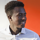 Handsome smiling young black man on orange and white divided background - PhotoDune Item for Sale