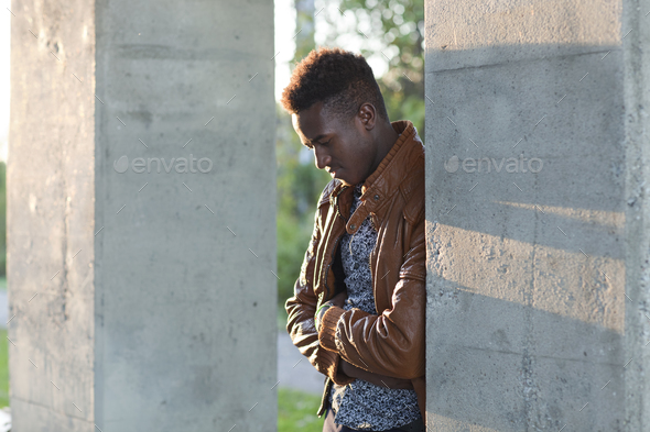 Young black man looking down leaning on a wall - Stock Photo - Images