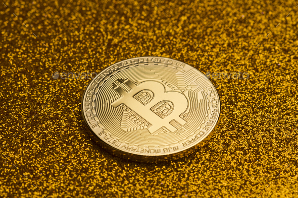 single bitcoin coin on golden glittering background - Stock Photo - Images