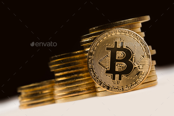 golden bitcoin in front of a pile of golden metallic coins on bl - Stock Photo - Images