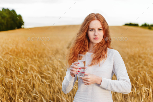 Young red-haired woman in field holding glass with drinking water - Stock Photo - Images