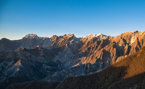 Apuane alpi snowy mountains and marble quarry at sunset in winte - Stock Photo - Images