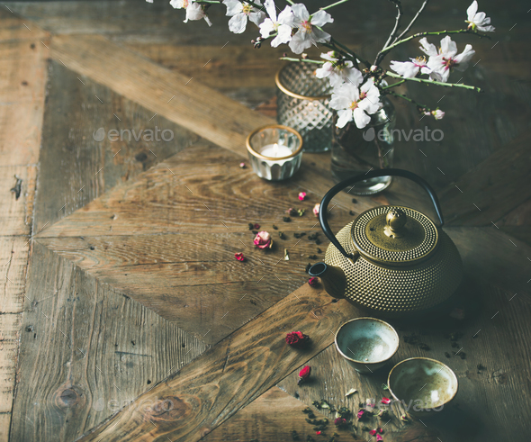 Asian golden iron teapot, cups, candles and almond blossom flowers - Stock Photo - Images
