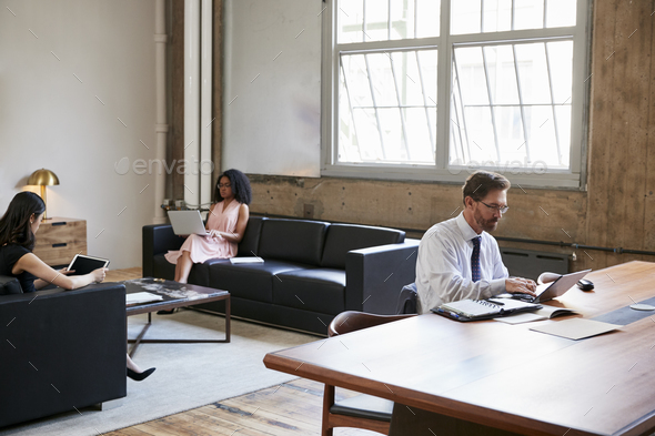 Businessman working at desk, colleagues on sofas, side view - Stock Photo - Images