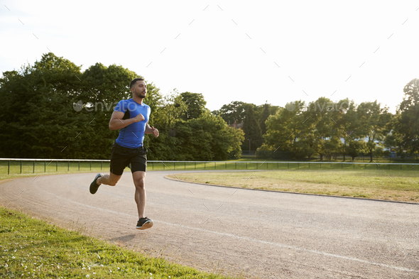 Young male athlete running at a track, full length - Stock Photo - Images