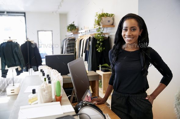 Female assistant smiling behind the counter in clothes store - Stock Photo - Images