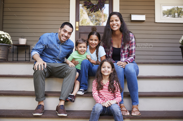 Portrait Of Family Sitting On Steps in Front Of House - Stock Photo - Images