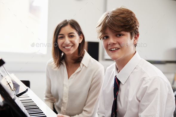 Portrait Of Pupil With Teacher Playing Piano In Music Lesson - Stock Photo - Images