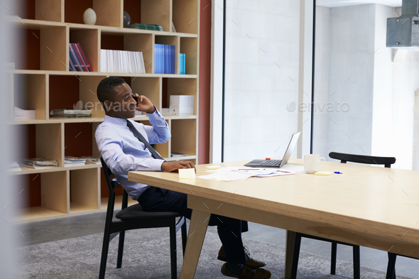 Young black businessman using smartphone in the boardroom - Stock Photo - Images