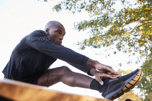 Young black man stretching leg on a bench in park, close up - Stock Photo - Images