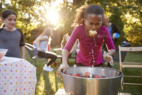 Pre-teen girl, apple in mouth, apple bobbing at garden party - Stock Photo - Images