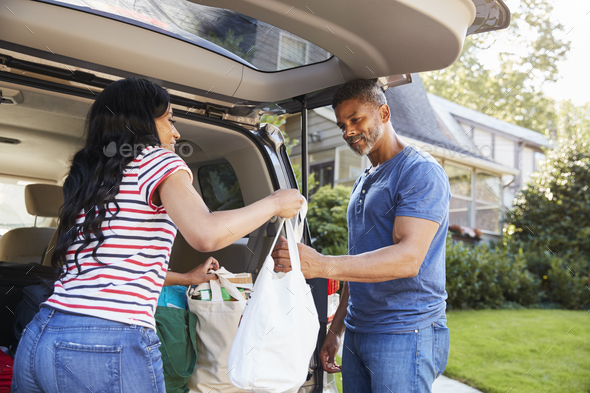 Couple Unloading Shopping Bags From Car - Stock Photo - Images