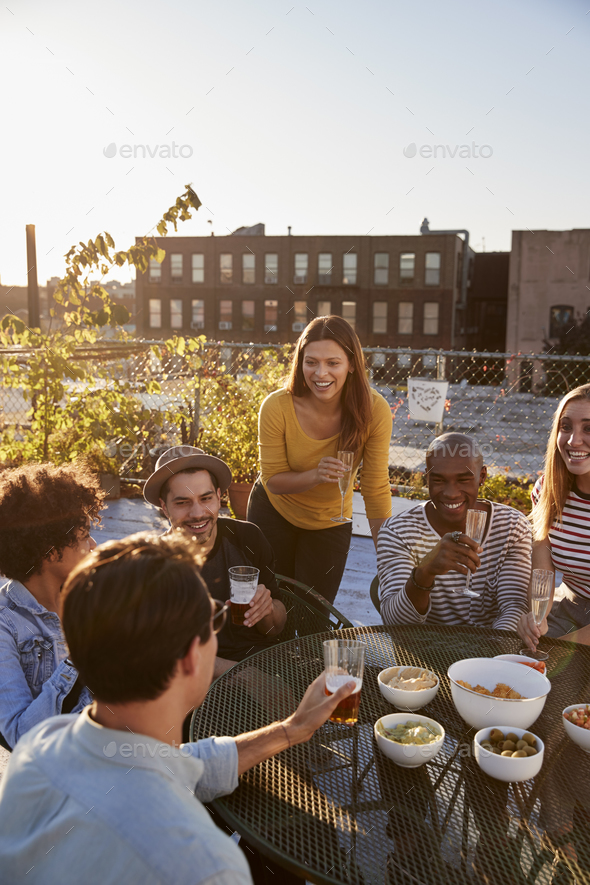 Friends talking at a party on a rooftop, vertical - Stock Photo - Images