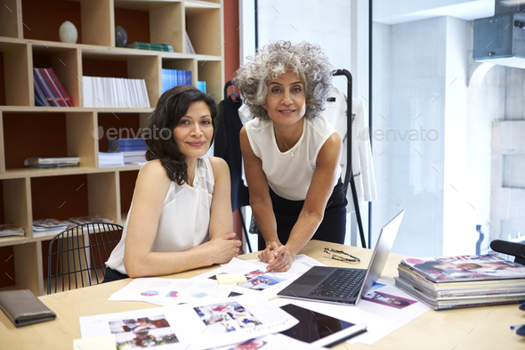 Two female creatives working in office looking to camera - Stock Photo - Images
