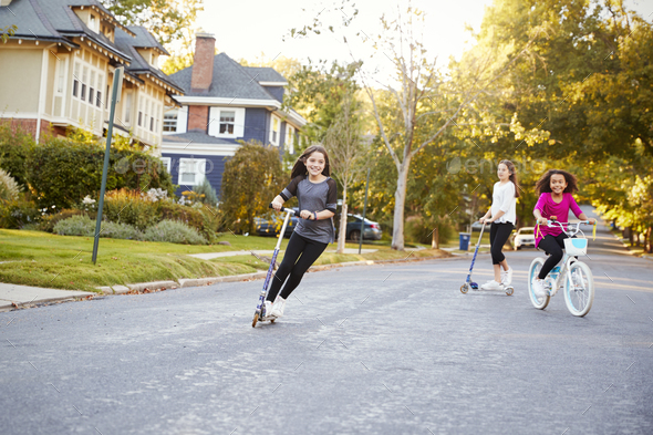 Three pre-teen girls playing in street on scooters and bike - Stock Photo - Images