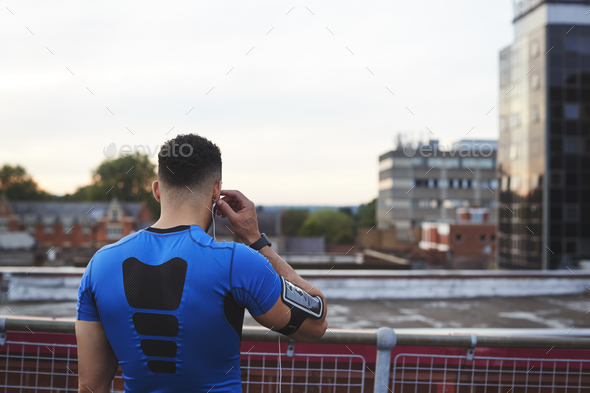 Male runner adjusting earphones in urban setting, back view - Stock Photo - Images