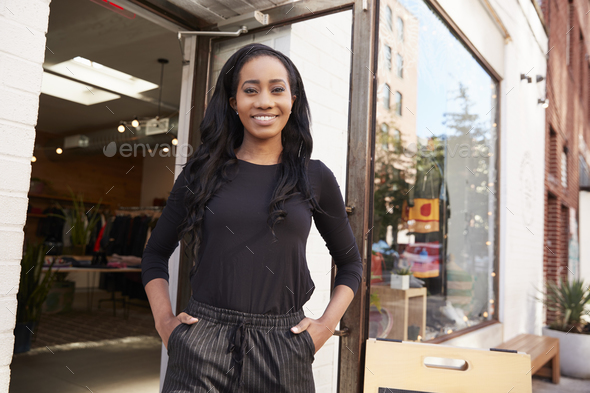 Young black woman smiling to camera outside her clothes shop - Stock Photo - Images