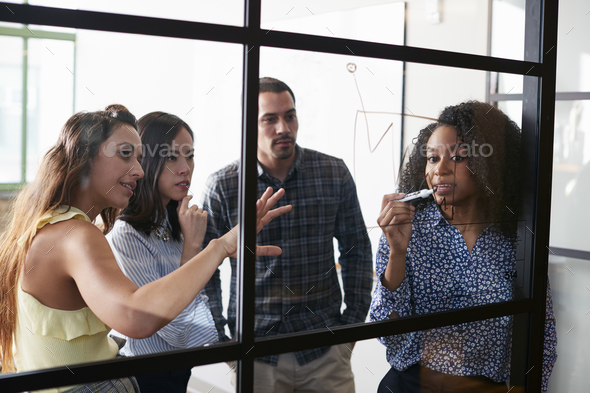 Young colleagues at a meeting visualising on a glass wall - Stock Photo - Images