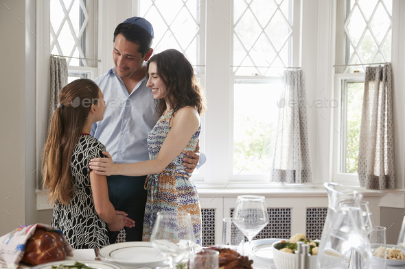 Jewish couple and daughter embracing before Shabbat meal - Stock Photo - Images