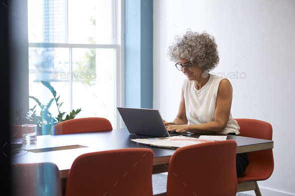 Smiling middle aged woman working alone in office  boardroom - Stock Photo - Images