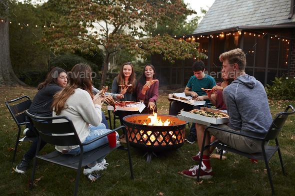 Teenage friends sit round a fire pit eating take-away pizza - Stock Photo - Images