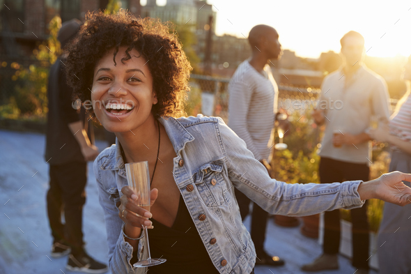 Young woman dancing at a rooftop party smiling to camera - Stock Photo - Images
