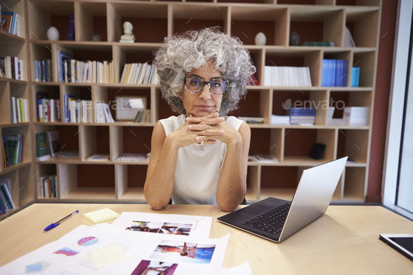 Senior businesswoman using laptop in office looks to camera - Stock Photo - Images