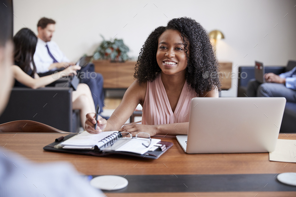 Young black woman at a desk looking to a colleague opposite - Stock Photo - Images