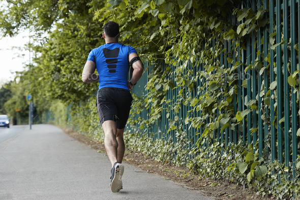 Back view of young male athlete running in the street - Stock Photo - Images