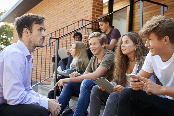 Teenage Students Talking To Teacher Outside School Buildings - Stock Photo - Images