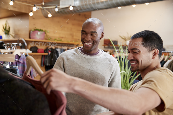 Two male friends look at clothes in a clothes shop, close up - Stock Photo - Images