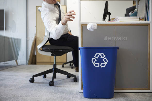 Man at desk throwing screwed up paper into recycling bin - Stock Photo - Images