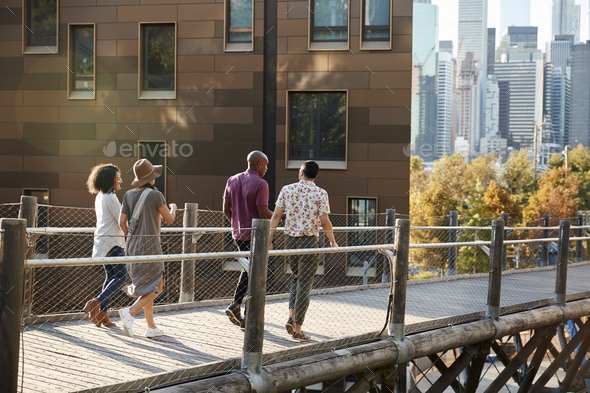 Group Of Friends Walking With Manhattan Skyline In Background - Stock Photo - Images