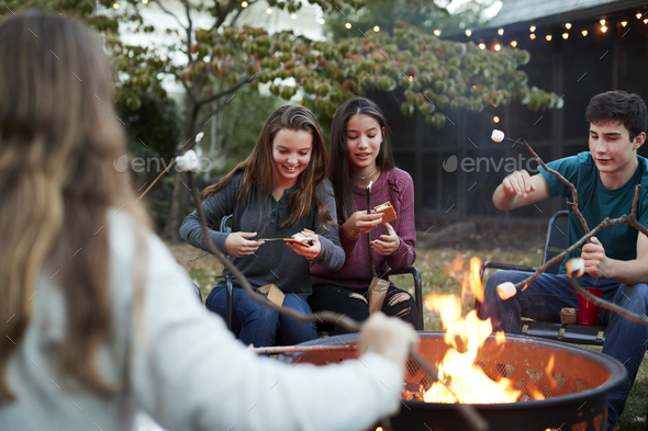 Teenage friends making somores with toasted marshmallows - Stock Photo - Images