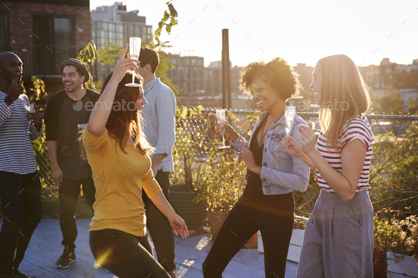 Female friends dancing and drinking at a rooftop party - Stock Photo - Images